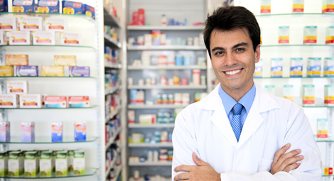 A pharmacist stood behind his counter with his arms folded